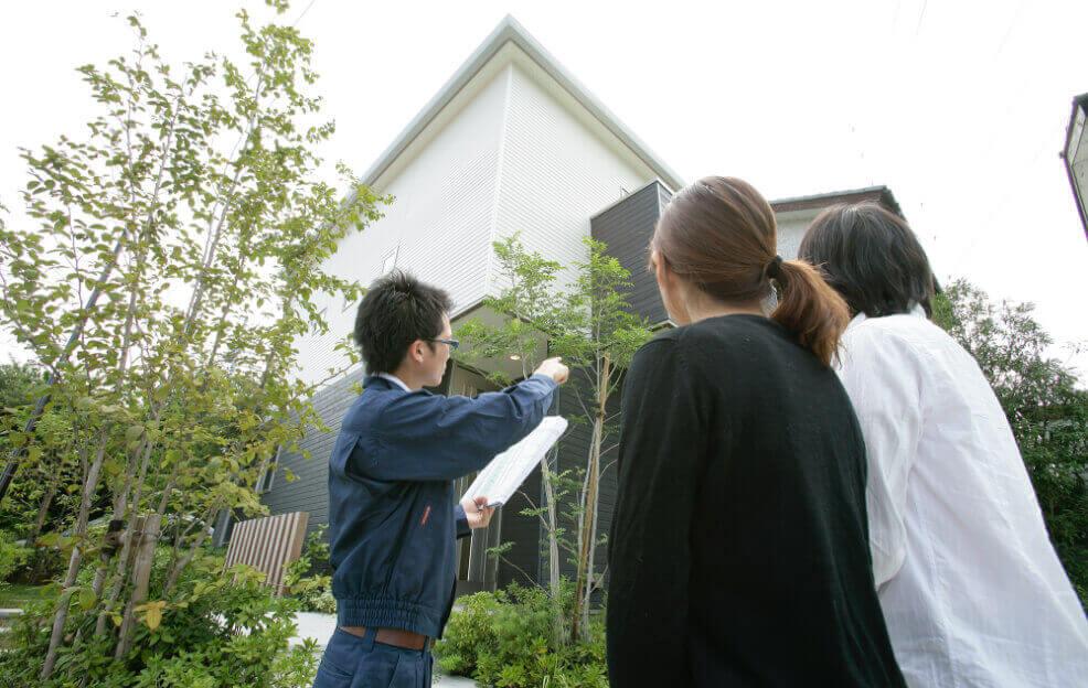 訪問をして家のメンテナンスについて確認する夫婦と社員