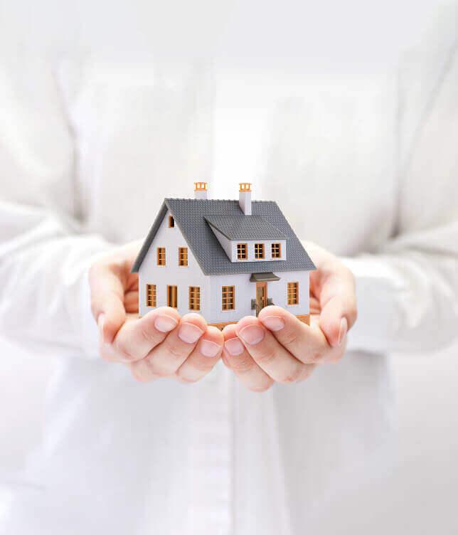 両手でお家の模型を抱える手