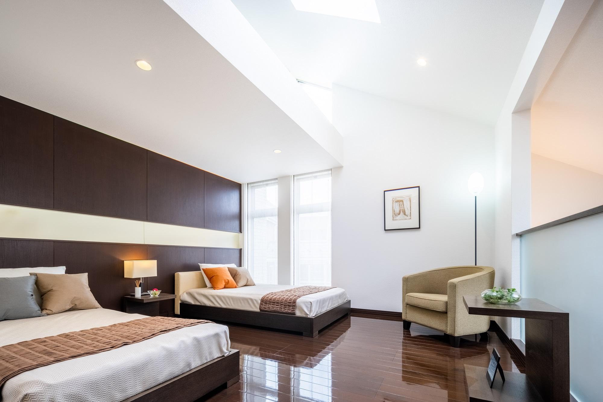勾配天井が開放的な主寝室。夜になると間接照明の温かな光が空間を包んでくれます。