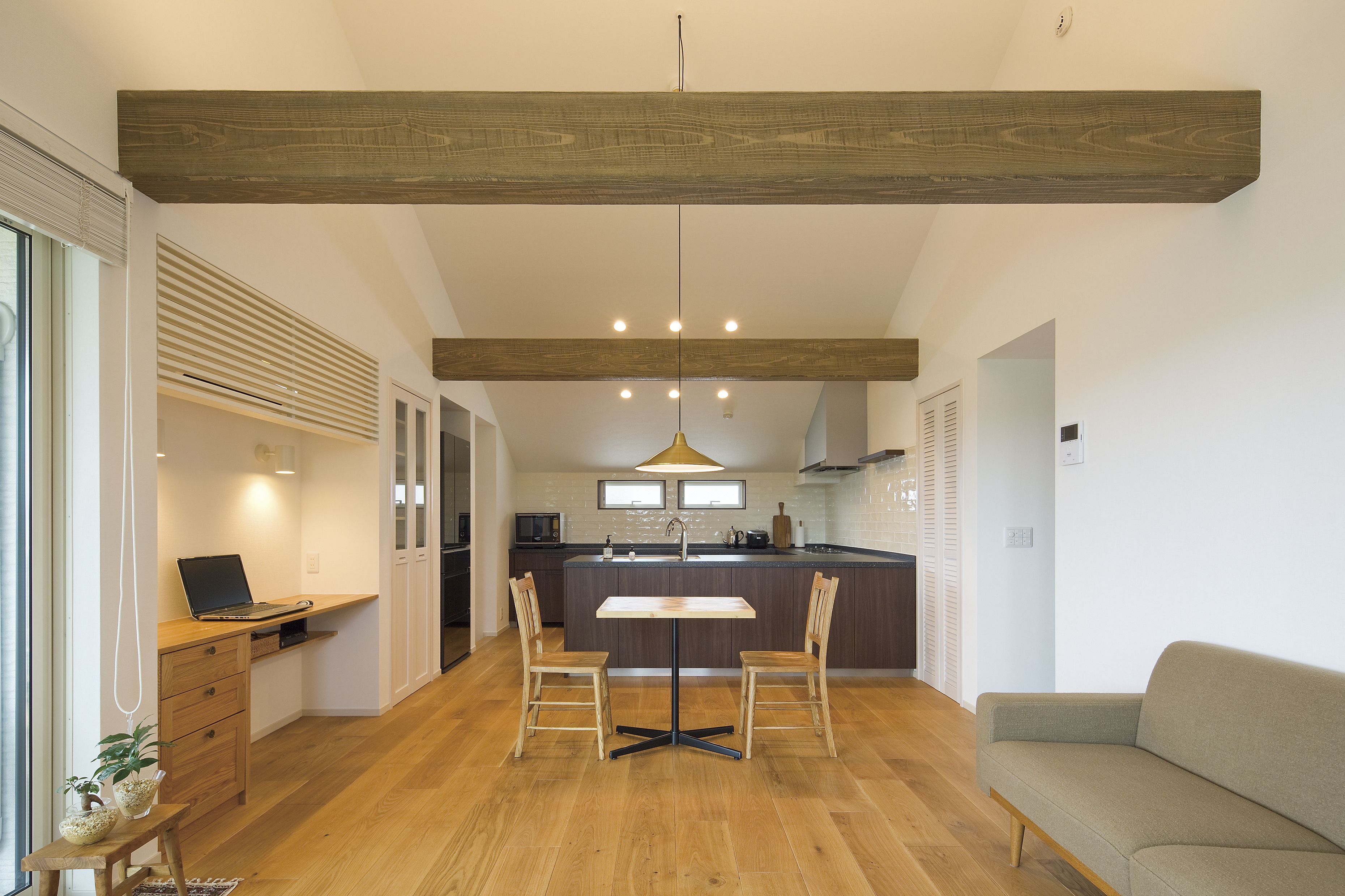 勾配天井の空間をよりキレイに見せるため、食器棚と冷蔵庫は壁面にぴったりと収まるビルトイン設計。