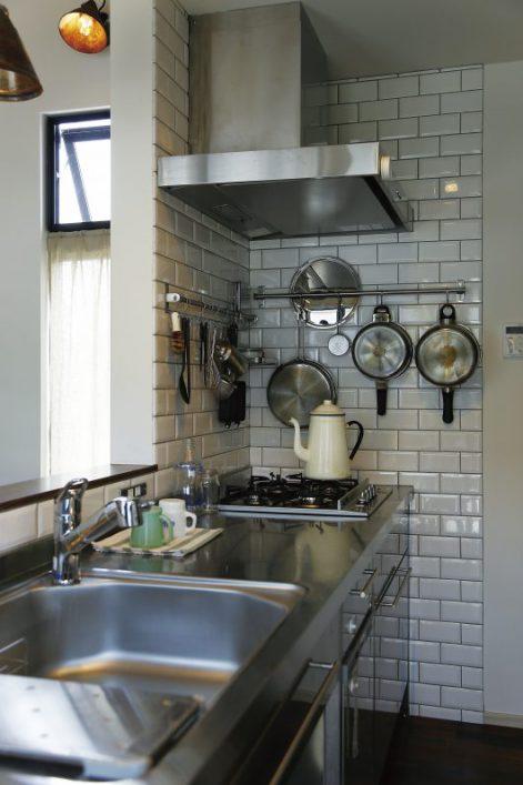 使い勝手の良いステンレス製のキッチンの壁は白いタイルで印象的に。