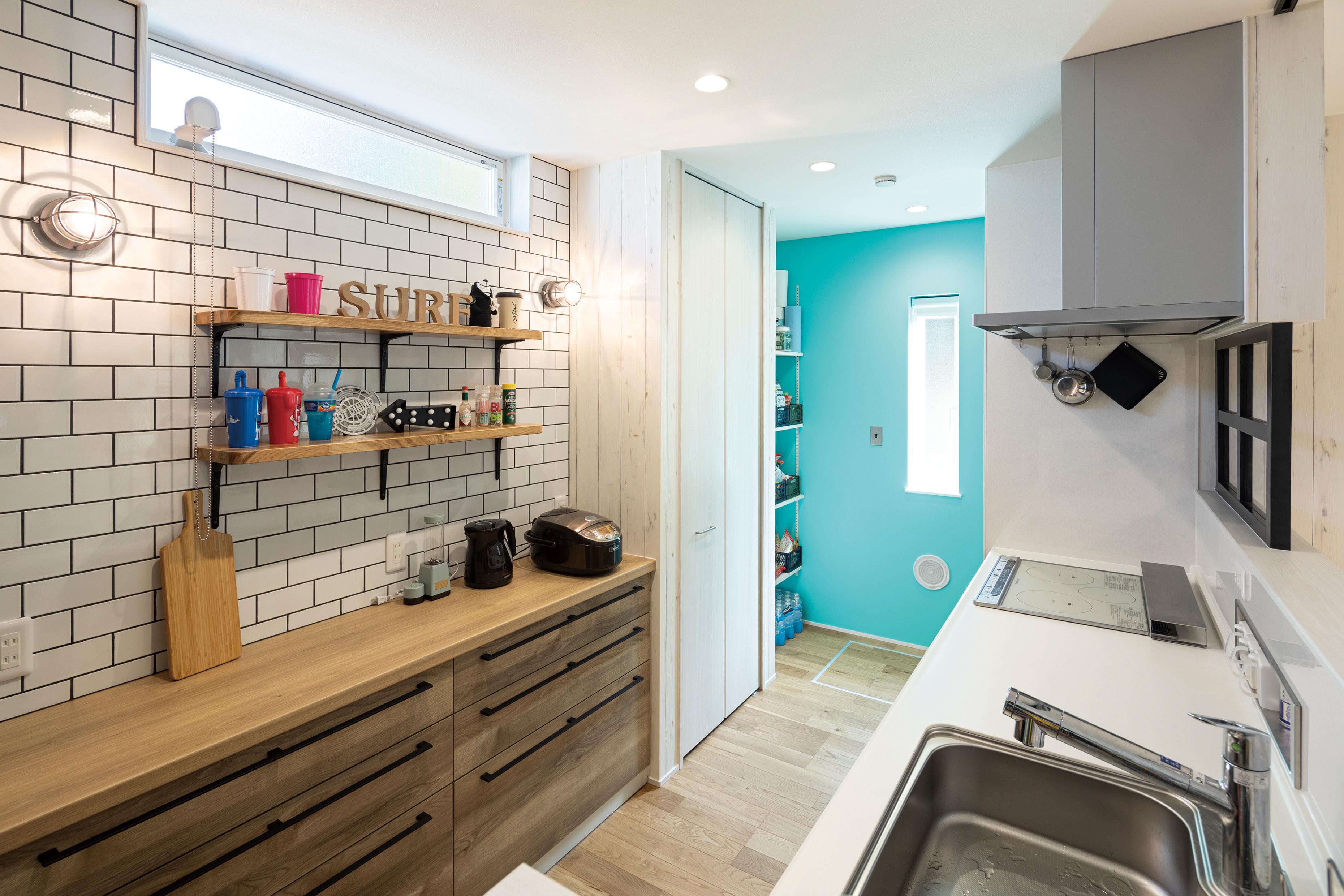 キッチン上は飾り壁をもうけ、タイルの壁とマリンライトで雰囲気を出しています。